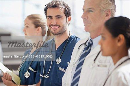 Portrait de l'infirmière souriante avec des médecins