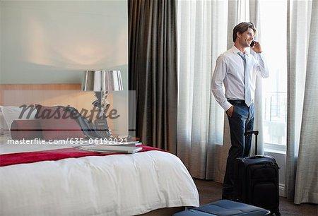 Kaufmann mit Koffer Gespräch am Handy am Fenster des Hotels Zimmer