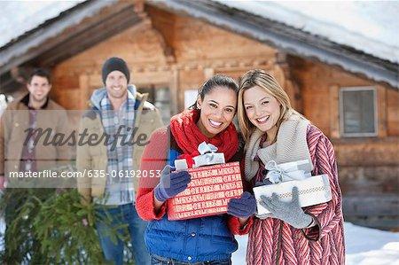 Portrait of smiling Friends holding Weihnachtsgeschenke vor Kabine