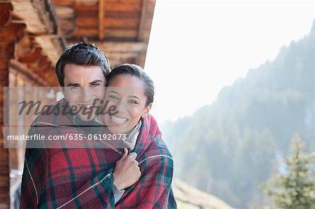 Portrait of smiling paar eingewickelt in eine Decke auf der Veranda der Hütte
