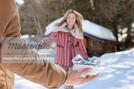 Frau läuft in Richtung Mann, hält Weihnachtsgeschenk im Schnee