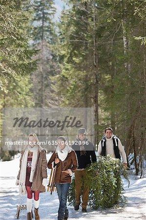 Lächelnd Paare mit frisch geschnittenen Weihnachtsbaum und Schlitten im verschneiten Wald