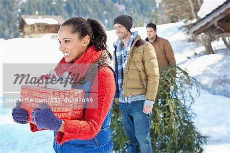 Lächelnd Freunde mit frisch geschnittenen Weihnachtsbaum und Geschenke im Schnee
