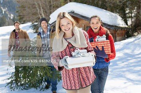 Portrait of smiling Paare mit frisch geschnittenen Weihnachtsbaum und Geschenke im Schnee