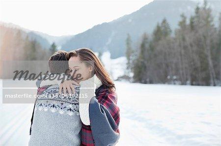Smiling woman hugging man in snowy field