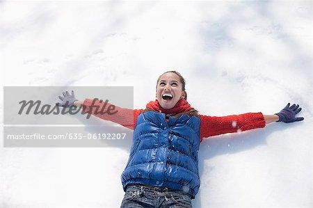 Femme souriante, faire des anges de neige
