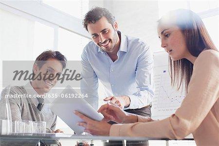 Le sourire des gens d'affaires à l'aide de la tablette numérique en réunion