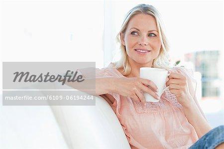 Beautiful blonde female sitting on her sofa