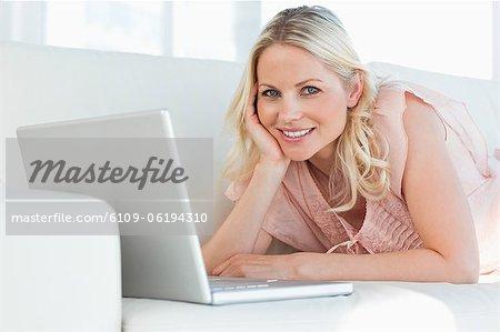 Süße Frau lächelnd beim liegen auf ihrem sofa