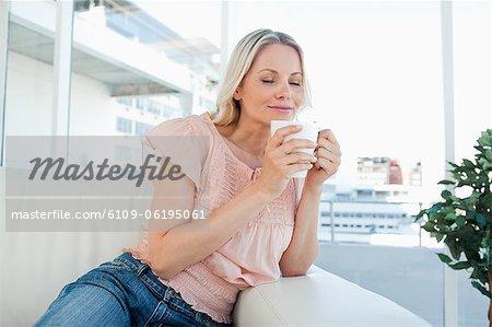 Blonde smelling her tea