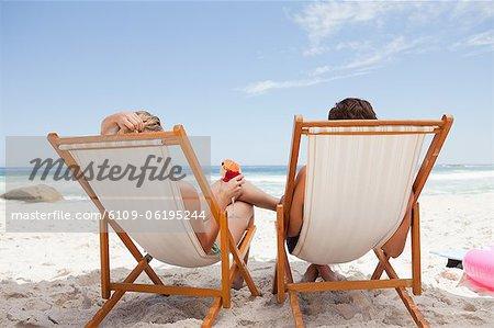 Vue arrière d'un jeune couple assis sur des chaises longues