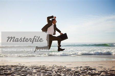 Jeune entrepreneur, sauter sur la plage avec sa serviette