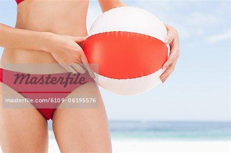Ballon de plage se tient sur une hanche womans
