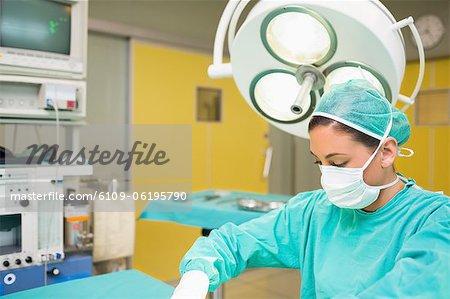 Weibliche Chirurg neben dem OP-Tisch