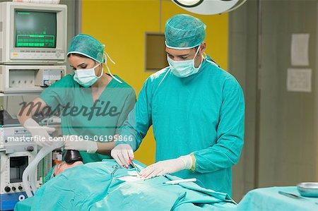 Arzt und Krankenschwester neben einem Patienten