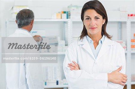 Pharmaciens de femme avec ses bras repliés et un collègue