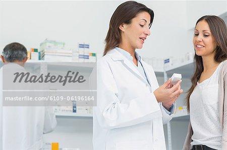 Pharmacien, parler à un client tout en maintenant les pilules