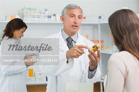 Apotheker zeigen einen Kolben der Pillen vor ein Kunde
