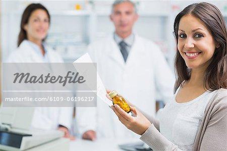 Client hält ein Papier und Pillen stehen in einer Apotheke
