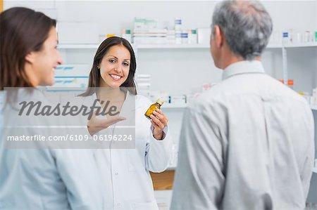 Präsentiert eine Flasche Pillen hinter der Theke einer Apotheke Apotheker