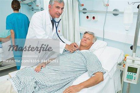 Souriant médecin de sexe masculin auscultating la poitrine d'un patient dans un service de chambre