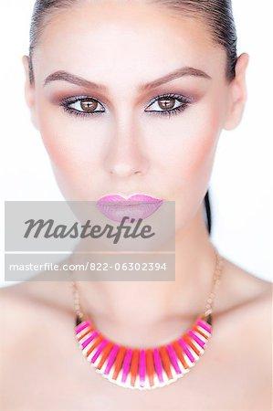 Frau trägt lila Lippenstift und Emaille Gold Halskette