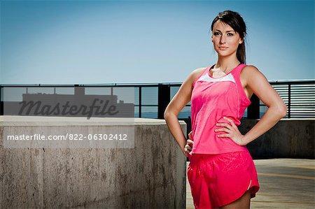 Junge Frau in Sportkleidung mit den Händen an den Hüften