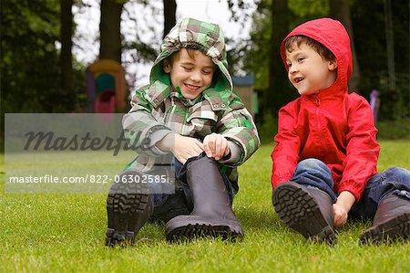 Deux garçons de chausser les bottes de Wellington à l'extérieur