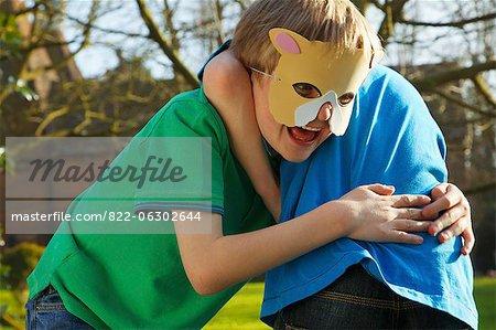 Garçon portant un masque de chat se battre avec ami