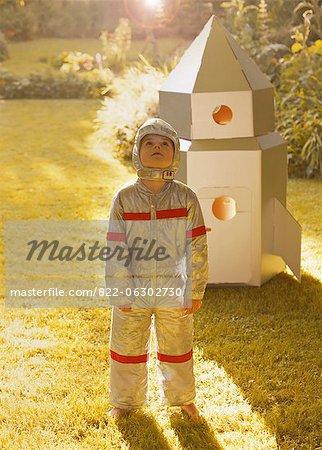 Boy Wearing Space Suit Standing in front of Cardboard Rocket Spacecraft