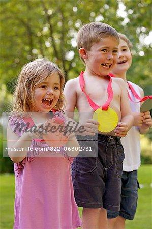 Lächelnd hält Karton Medaillen Kinder