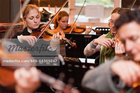 Geigenspieler üben mit Gruppe
