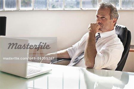 Unternehmer denken am Schreibtisch