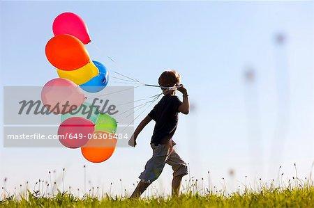 Garçon avec des ballons colorés dans l'herbe