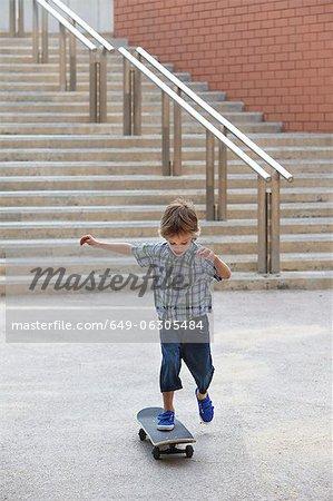 Garçon jouant avec planche à roulettes à l'extérieur