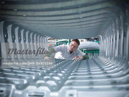 Travailleur en inspectant les pressages de corps de voiture en usine automobile