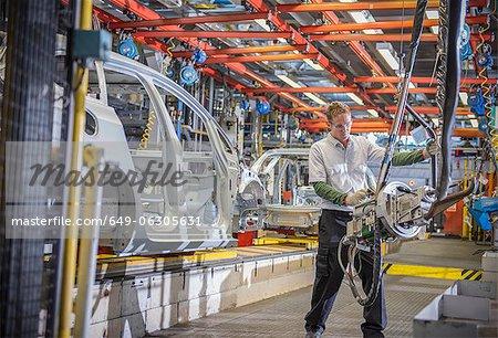 Travail avec des carrosseries et des machines sur la ligne de production en usine automobile