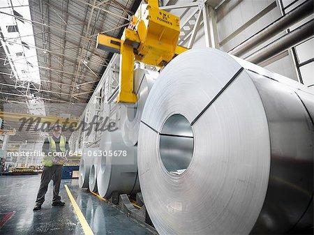 Travailleur d'exploitation grue avec acier roule en usine automobile