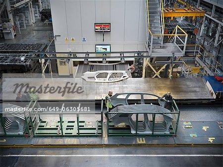 Vue d'angle élevé des travailleurs qui manipulent des pièces de voiture comme ils sortent de la presse en usine automobile