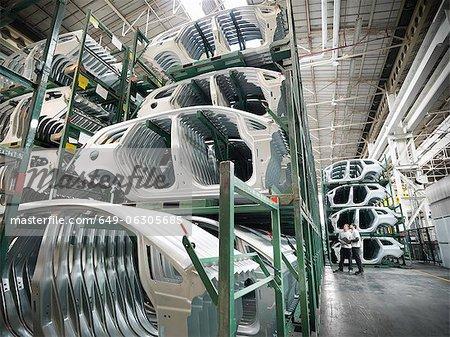 Ingénieurs avec des pièces de voiture pressé en usine automobile