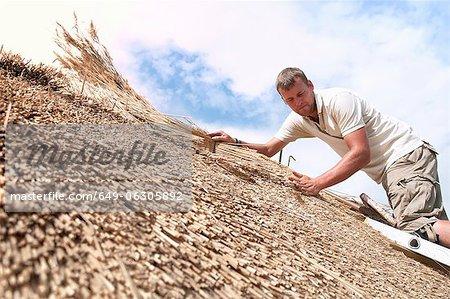 Homme travaillant sur le toit de paille