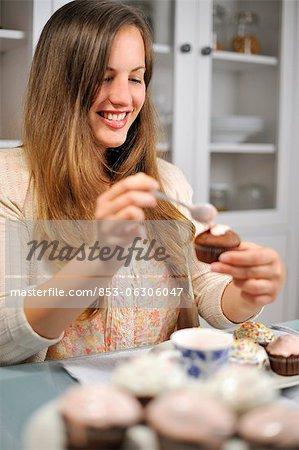 Young woman garnishing muffin