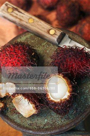 Ein Rambutan mit zwei ganze Rambutans geschält; Messer