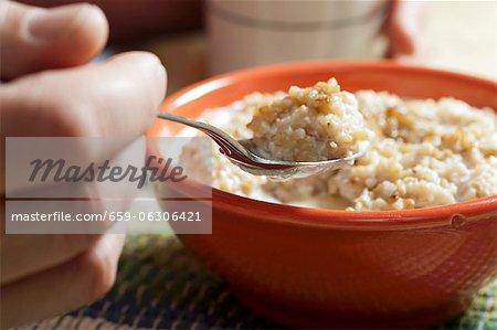 Main tenant une cuillerée de farine d'avoine dans un bol