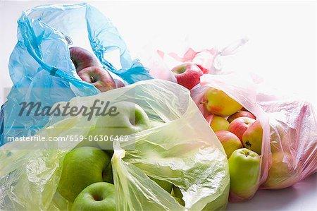 Divers types de pommes dans un sac en plastique