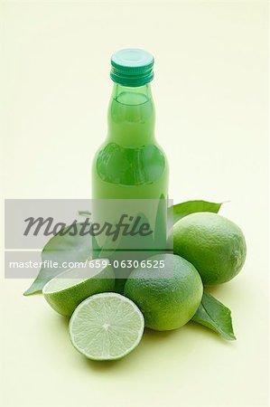 Une bouteille de jus de lime et limes fraîches
