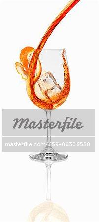 Aperol in ein Glas mit einem Eiswürfel gegossen