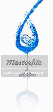 Un cocktail bleu étant versé dans un verre avec des glaçons