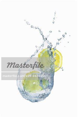 Une éclaboussure de l'eau avec des tranches de citron