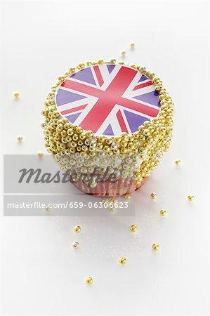 Un petit gâteau décoré avec une Union Jack et boules de sucre